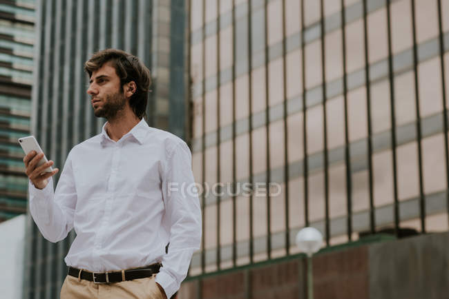 Portrait of confident businessman in white shirt holding smartphone and looking aside at urban scene — Stock Photo