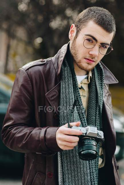 Portrait of stylish man in eyeglasses with analog camera at street — Stock Photo