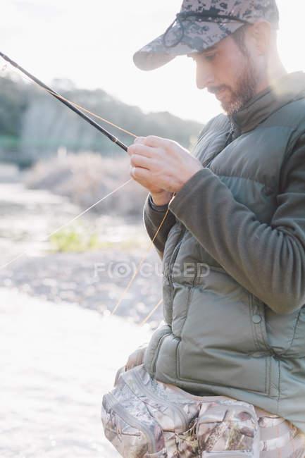 Vista lateral de hombre preparando anzuelo para la pesca en el río - foto de stock