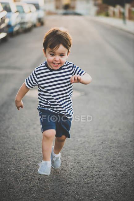 Retrato de menino surpreso correndo com a boca aberta em estrada de asfalto — Fotografia de Stock
