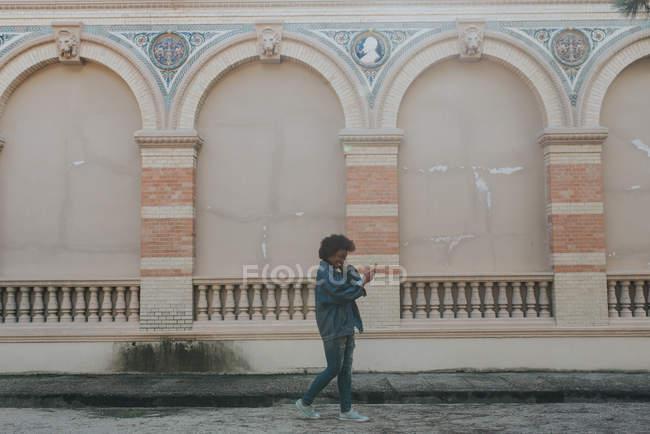 Vista laterale della ragazza in vestiti del denim rendendo selfie sopra la vecchia parete di bassorilievo — Foto stock
