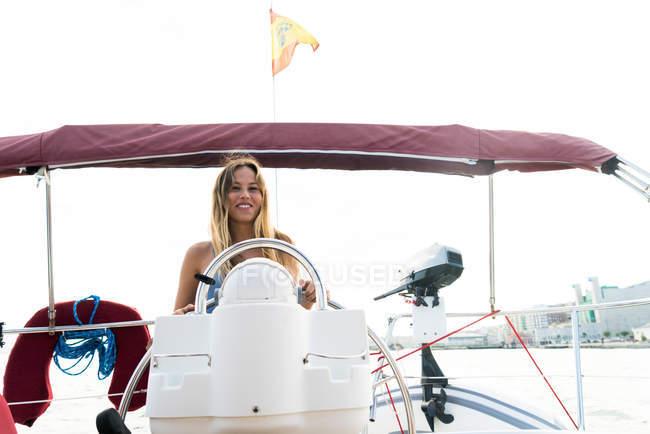 Vue de face de jeune fille debout à la barre sur le pont d'yacht sur la journée ensoleillée — Photo de stock