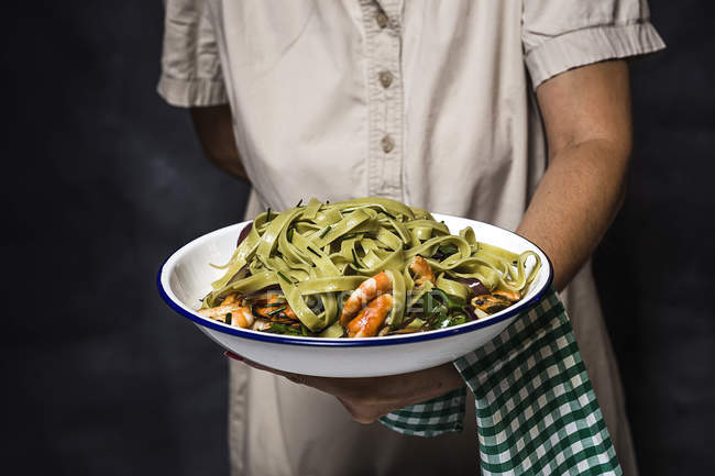 Midsection of woman giving plate of italian green tagliatelle with seafood — Stock Photo