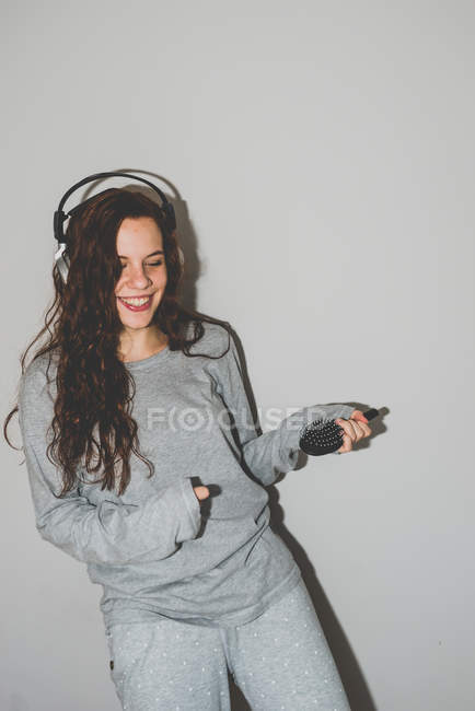 Woman wearing headphones playing air guitar — Stock Photo