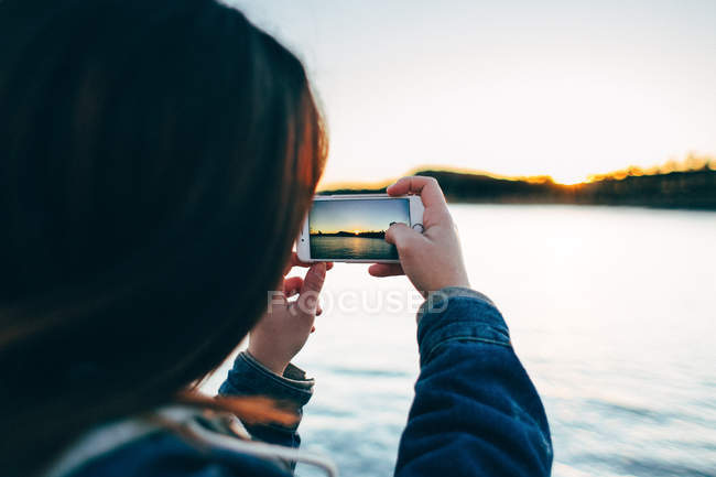 Over shoulder view of woman taking photo of sunset on smartphone. — Stock Photo