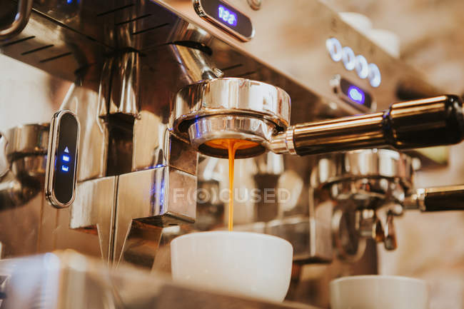 Low angle view of coffee machine pouring coffee in white cup — Stock Photo
