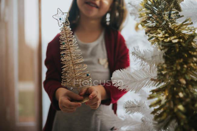 Ritagliare la ragazza sorridente che tiene il piccolo albero di Natale decorativo — Foto stock
