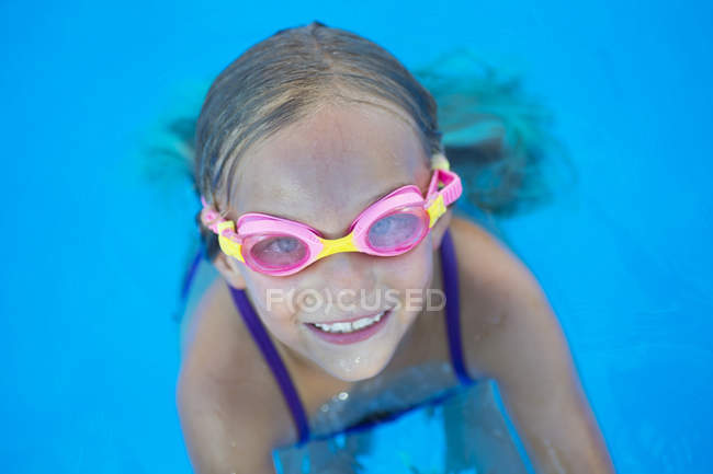 Cheerful kid in goggles at swimming pool — Stock Photo