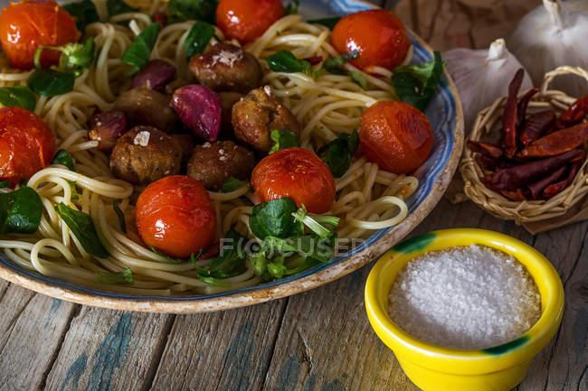 Крупним планом подання пластину з Італійська паста з фрикадельки, Вишневі помідори, подається з сіль і перець в креманки — стокове фото