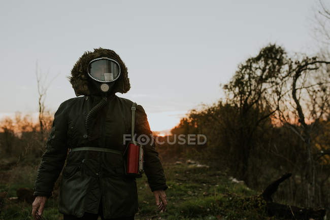 Portrait of man wearing gas mask and standing in field at sunset time — Stock Photo