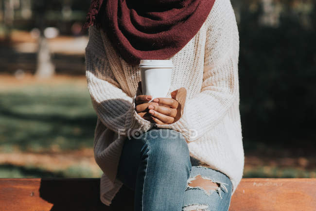 Mid section view of female sitting on bench back at park and holding cup of coffee — Stock Photo