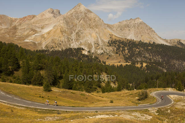 Scenic landscape with cyclists riding on road in mountains — Stock Photo