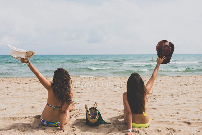 Rear view of two girlfriends in bikini sitting on beach with hats in raised arms — Stock Photo