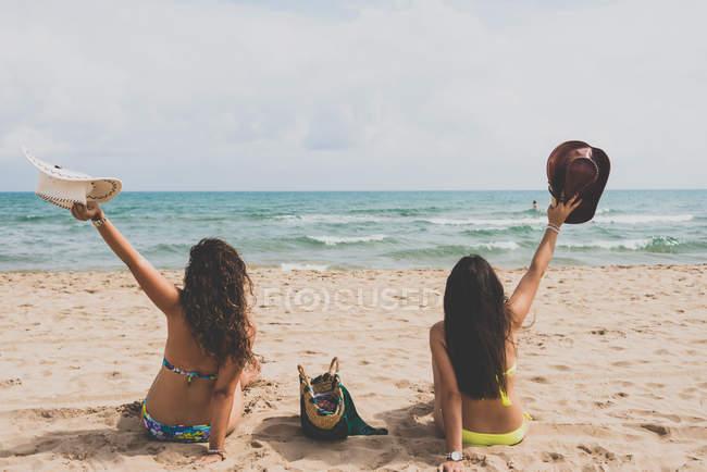 Вид сзади две подружки в бикини, сидя на пляже с шляпы в поднятыми руками — стоковое фото