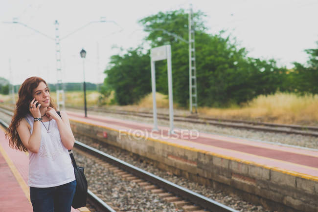 Portrait of young girl with red hair talking over smartphone on railway countryside platform — Stock Photo