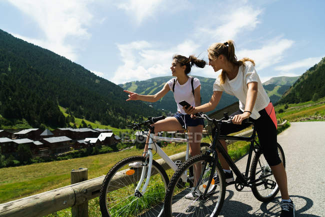 Girls on bicycles using smartphone at mountain countryside — Stock Photo