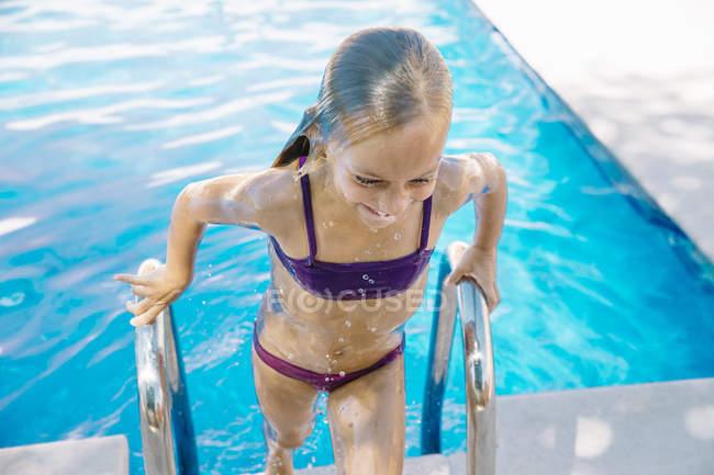 Niña en traje de baño para subir escaleras de piscina sonriendo. - foto de stock