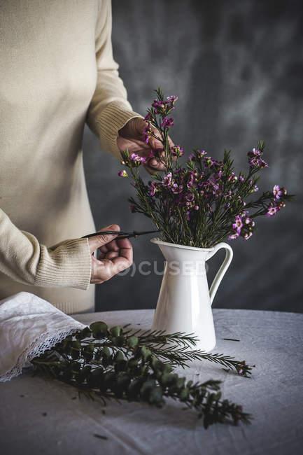 Immagine ritagliata di fiorista femminile che taglia con forbici bouquet di fiori in vaso bianco — Foto stock