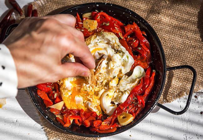 Dessus de main ingrédient mettre en casserole avec oeufs brouillés et tomates séchées — Photo de stock