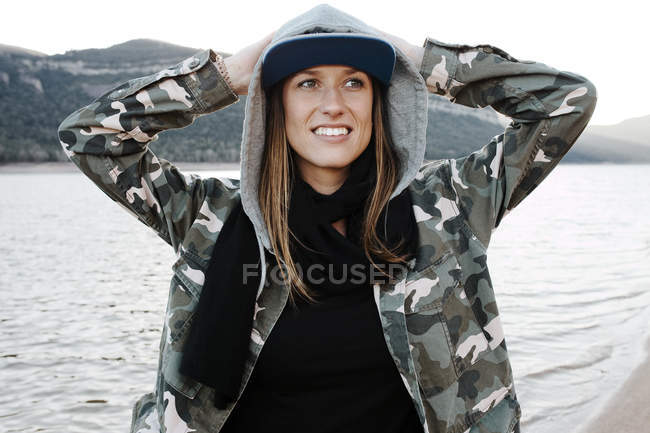 Stylish woman in hoodie standing with hands up and looking cheerfully away — Stock Photo