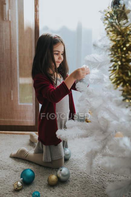 Vista laterale della ragazza adorabile che si siede sul pavimento e mettendo le bagattelle sull'albero di Natale decorativo bianco — Foto stock