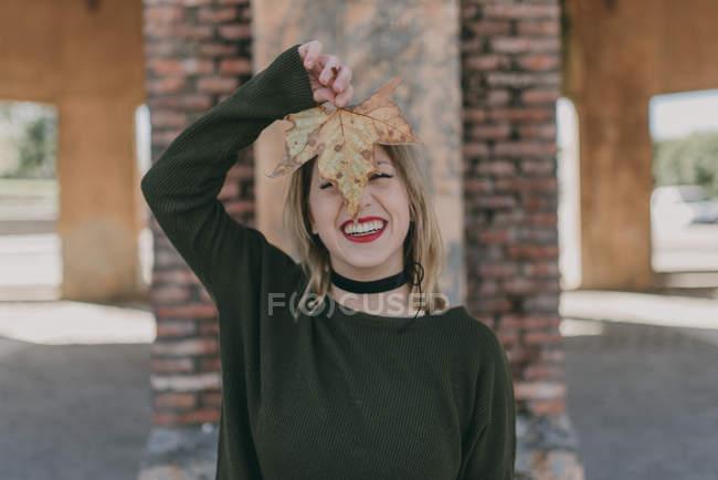 Дівчинка тримає Осіннє листя проти обличчя — стокове фото