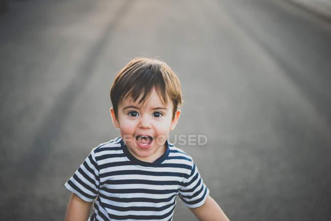 Portrait d'un petit garçon surpris regardant une caméra à bouche ouverte sur une route asphaltée — Photo de stock
