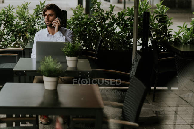 Distant view of smiling businessman sitting at table and talking over smartphone while using laptop at cafe terrace — Stock Photo