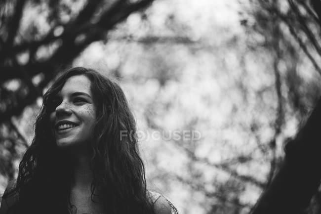 Життєрадісна дівчина фотографіях хтось дивитися вбік при лісів — стокове фото