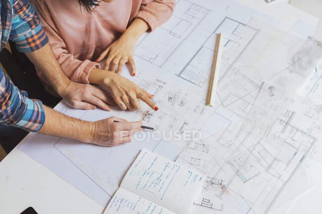 Чоловічі руки вказують олівцем на креслення. — стокове фото