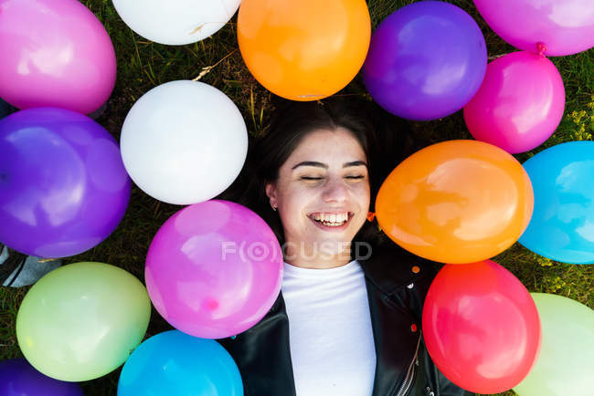 From above woman smiling with eyes closed on grass with balloons. — Stock Photo