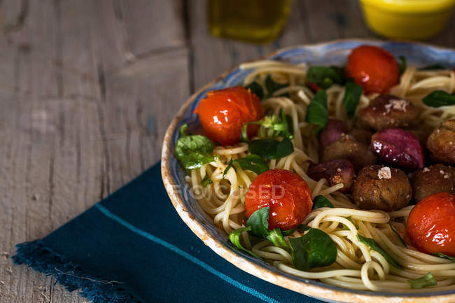 Crop image of plate of pasta with meatballs and cherry tomatoes on towel over rustic wooden table — Stock Photo