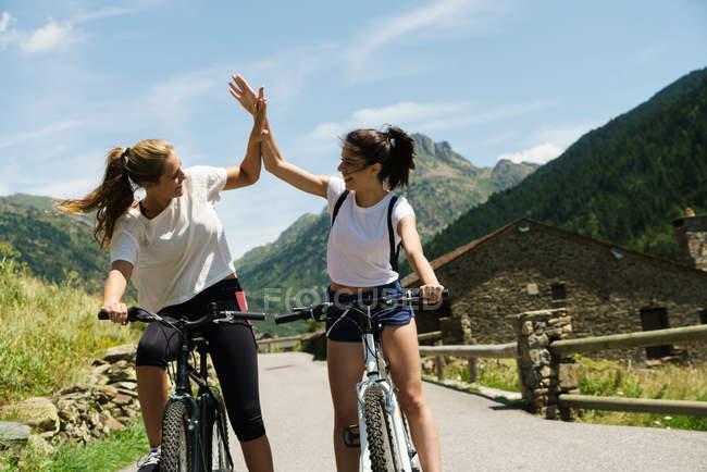 Девушки на велосипедах дают пять — стоковое фото