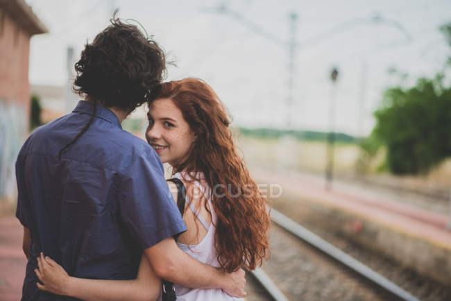Back view of  girl looking over shoulder at camera while hugging with boyfriend at countryside rail platform — Stock Photo