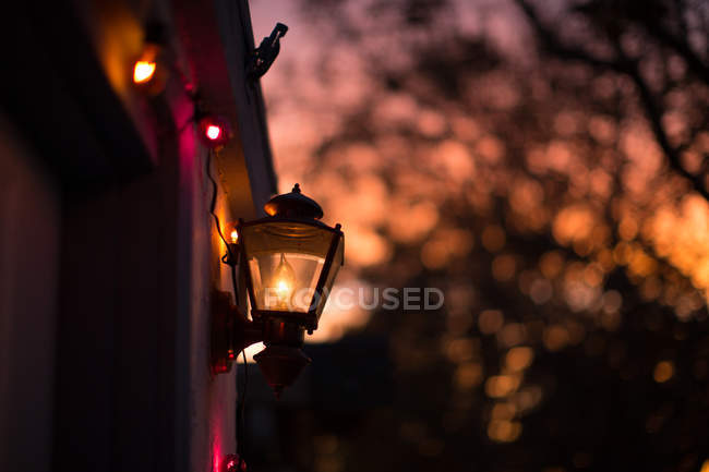 Crop facade decorated with fairy lights and lamp at evening dusk — Stock Photo