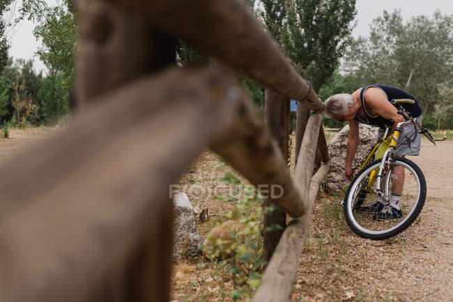 Vista lateral do homem sênior dobrando-se sobre a bicicleta e ajustando a cadeia de bicicletas — Fotografia de Stock
