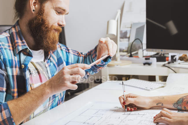 Man and woman sitting at the table in office and working on proj — Stock Photo