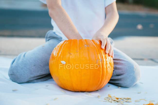 Garçon méconnaissable sculptant une citrouille d'Halloween avec les mains. — Photo de stock