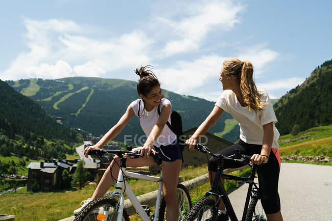 Girls riding bikes in countryside — Stock Photo