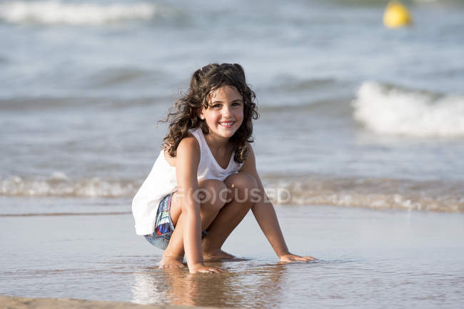 Curly girl sittin at beach and looking at camera — Stock Photo