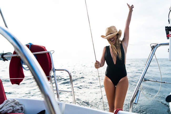 Portrait of blonde girl in straw hat posing on yacht deck over ocean waves on background — Stock Photo