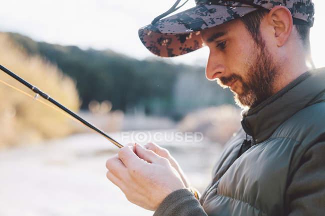 Retrato de hombre maduro preparación de gancho para la pesca en el río - foto de stock