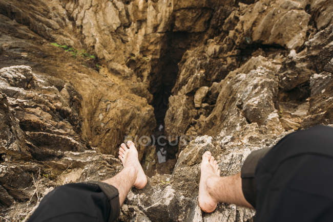 Looking down view of bare feet over rocky cliffs — Stock Photo