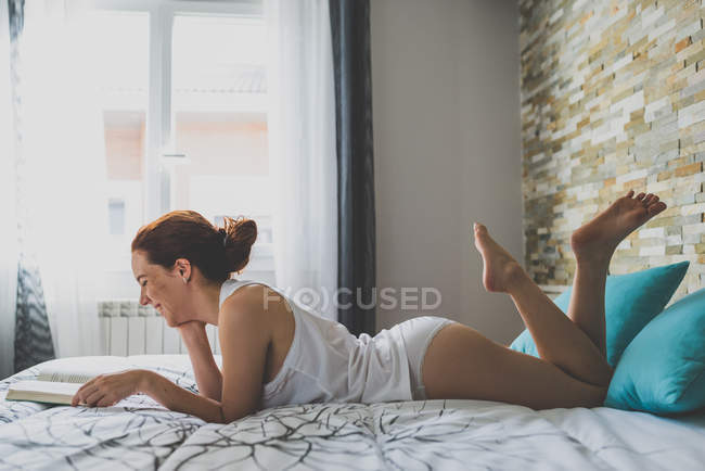 Smiling girl is reading a book — Stock Photo