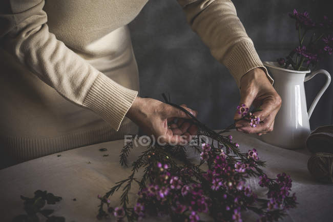 Mid section of female florist cutting pink flower with scissors on table with vase — Stock Photo