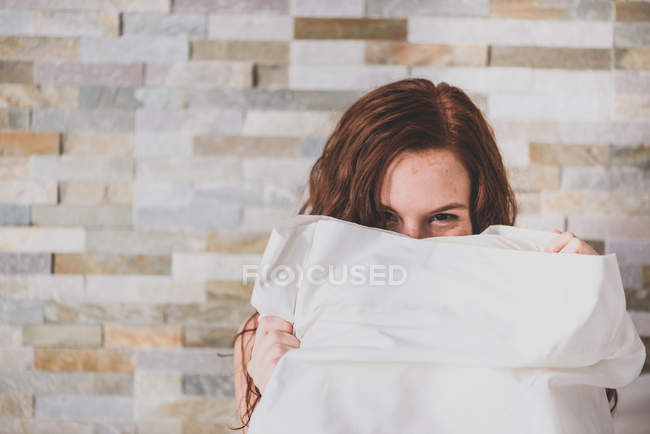 Menina, escondendo o rosto com o travesseiro e olhando para a câmera — Fotografia de Stock