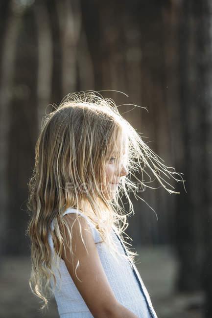 Вид збоку білява дівчинка постановки в сонячному світлі — стокове фото