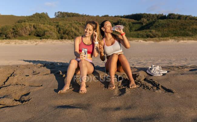 Mulheres bebendo água e descansando depois da formação profissional na praia — Fotografia de Stock