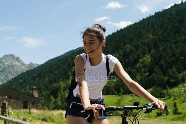 Girl riding bicycle at mountain countryside — Stock Photo