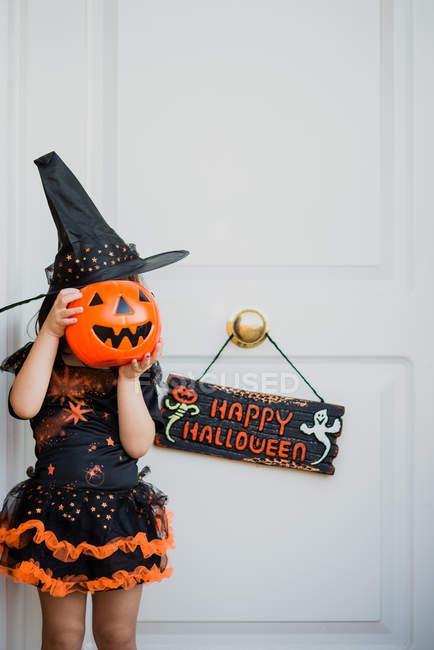 Jeune fille en costume de sorcière se cachant le visage avec sac citrouille — Photo de stock